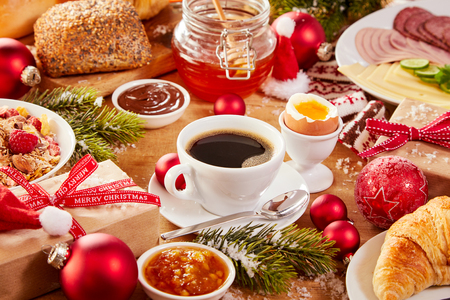 Christmas Intercontinental breakfast table with an assortment of tasty fresh food, coffee, gifts and colorful red decorations sprinkled with winter snow Фото со стока