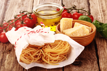 Rolled self made spaghetti pasta with ingredients for preparing Italian cuisine including Parmesan cheese, vine tomatoes and olive oil