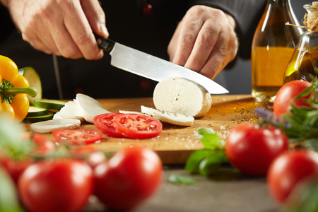 Chef making traditional Italian Caprese salad slicing mozzarella cheese with a large knife with tomatoes and basil in the foreground Imagens