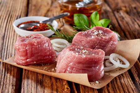 Close up of three pork medaillions on wooden background with various spices for great menu. 스톡 콘텐츠