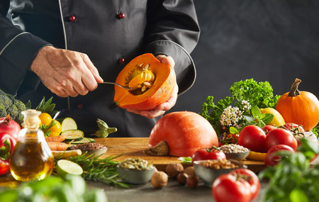Chef in black scooping seeds out of small pumpkin bordered by multiple different kinds of vegetables