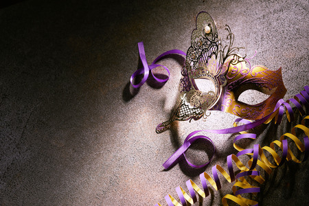 Overhead view of small gold metal mask sitting on the ground next to orange and purple spiraled ribbons