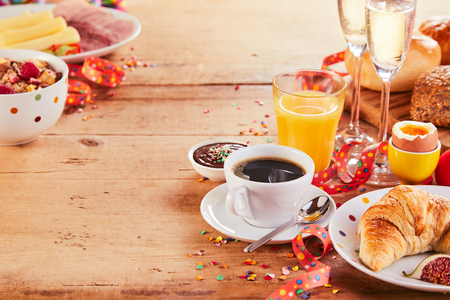 Festive carnival breakfast borders with streamers, confetti and champagne on a wooden table