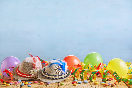 Celebratory hats with feathers stuck in them and multicolored balloons sitting on rustic wood plank table