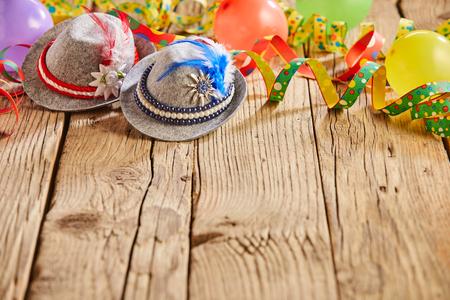Małe czapeczki z wbitymi w nie piórkami i okrągłymi wielokolorowymi balonami siedzącymi na rustykalnym drewnianym stole