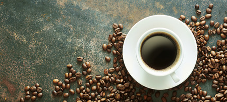 Cup of hot espresso coffee with full roast beans on a textured slate background with copy space Stock fotó