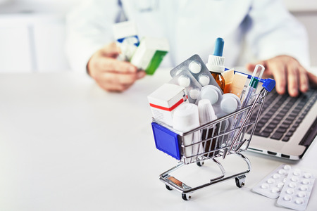 Close-up of various medicines in a small shopping cart on the desk of a drugstore with electronic payment as concept for costs and healthcare