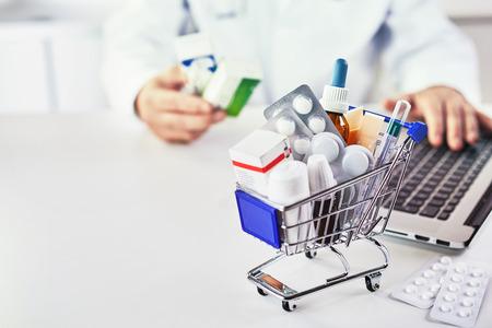 Gros plan sur divers médicaments dans un petit panier sur le bureau d'une pharmacie avec paiement électronique comme concept de coûts et de soins de santé