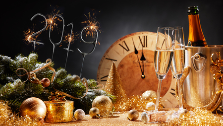 New Years Eve 2019 party background with flutes of champagne, decorations, and a clock counting down to midnight Standard-Bild - 110080906