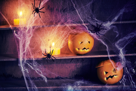 Spooky Halloween jack-o-lanterns y arañas entrelazadas con telarañas en viejos estantes de madera con velas brillando en las sombras Foto de archivo