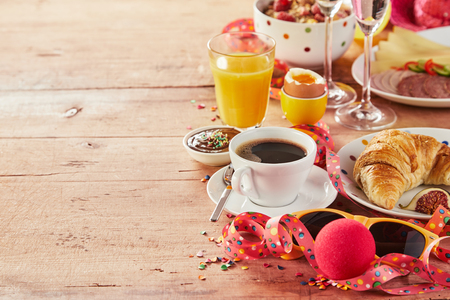Carnival breakfast border with party accessories amidst a tasty spread of cereal, coffee, cheese, meat, egg, orange juice and croissant, copy space on wood Stock Photo