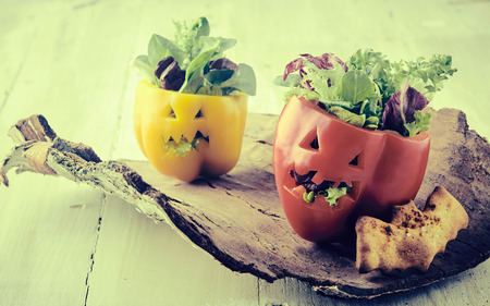 Rustic vintage Halloween food table decorations with carved faces on fresh bell peppers stuffed with salad with faded effect
