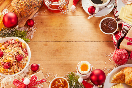Christmas Intercontinental breakfast food frame with copy space on a wooden table with colorful Xmas gifts Stock Photo