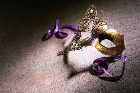 Decorative gold butterfly design carnival mask with purple ribbons in a shaft of light on a textured grey background with copy space