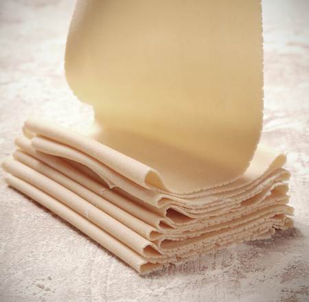 Folded sheet of raw durum wheat dough ready for preparing Italian pasta on a floured kitchen table in square format