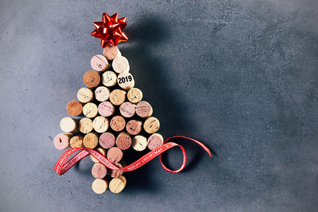 Creative 2019 wine cork Christmas tree decorated with a red foil ribbon and bow over a mottled blue background