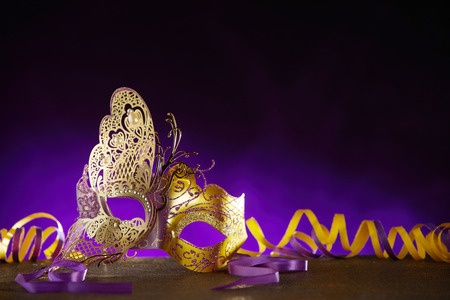 Carnival or Mardi gras background with a decorative face mask in the shape of a gold butterfly