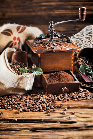 Hessian bag of roasted coffee beans with old wooden mill with an open drawer filled with fresh ground coffee on an old rustic wood table with copy space Stock Photo