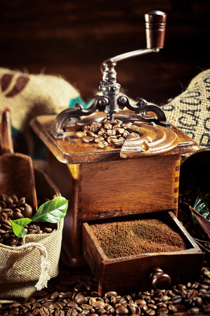 Vintage coffee still life with old wooden grinder with an open drawer filled with freshly ground coffee on a bed of roasted beans