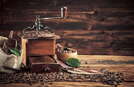 Old vintage coffee mill with roasted beans and a drawer full of ground coffee on a rustic table with copy space