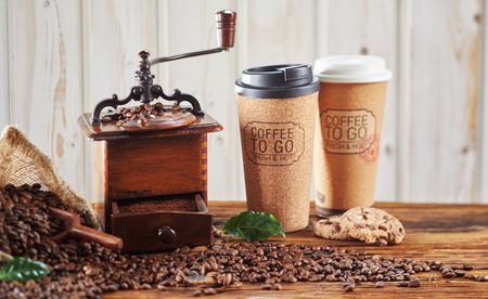 Vintage wooden coffee grinder with ground coffee and roasted beans with two takeaway Coffee To Go cups on a rustic wooden table