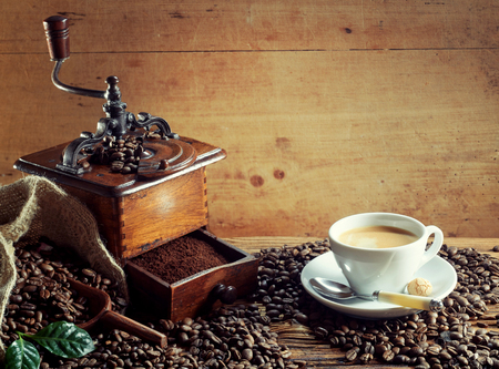 Old wooden coffee grinder with cup of latte milk coffee and scattered roasted beans on a rustic wood background with copy space