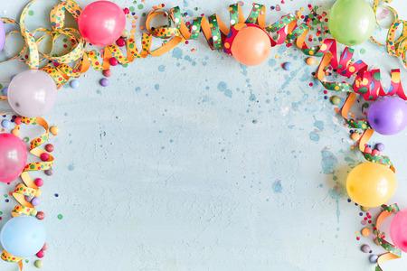 Carnaval-, festival- of verjaardagsballonachtergrond met kleurrijke feestwimpels, snoep en confetti die een rand maken op een blauwe achtergrond met kopieerruimte Stockfoto