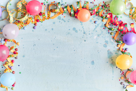 Carnival, festival or birthday balloon background with colorful party streamers, candy and confetti making a border on a blue background with copy space Stockfoto