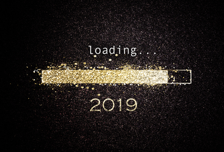 Computer screen with loading bar counting down for New Years Eve 2019 with sparkling glitter and copy space over black 免版税图像