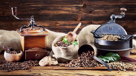 Coffee still life with old vintage roaster and grinder, hessian bags and raw and roasted coffee beans over a rustic wood background
