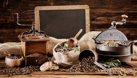 Vintage coffee roaster and grinder with raw and roasted coffee beans in hessian bags in front of an old blank school slate with copy space