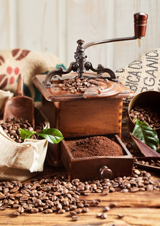 Coffee grinder with ground coffee and scattered roasted beans spilling from a burlap sack onto a rustic wooden table Stock Photo