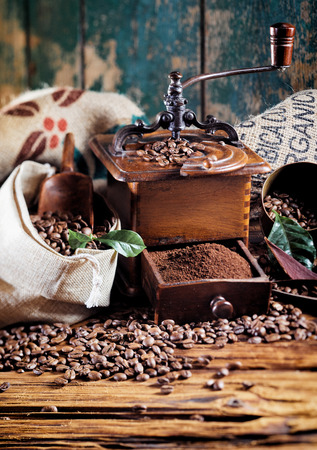 Retro wooden coffee mill with roasted beans and an open drawer of ground coffee on an old rustic wooden table