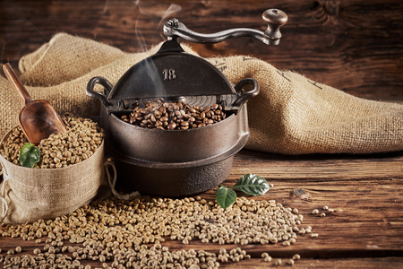 Vintage cast iron coffee roaster with raw beans spilling from a hessian bag onto a rustic wood table