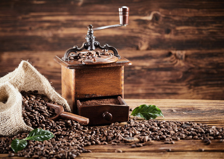 Rustic wooden coffee mill with beans spilling from a burlap bag onto an old weathered wood table with copy space Stok Fotoğraf