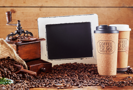 Roasted coffee beans with old wooden grinder, slate and two takeaway Coffee To Go coffee cups in a rustic still life