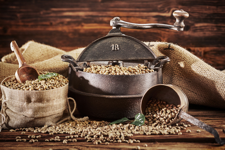 Cast iron vintage coffee roaster with raw beans spilling from a hessian bag onto a rustic wood table in a close up still life Stock Photo