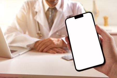 Patient holding a blank mobile phone at a medical consultation with the screen with copy space visible to the viewer