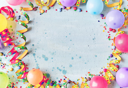 Multicolored carnival or birthday background on blue with a frame of colorful party balloons, streamers, confetti and candy around central copy space Stockfoto