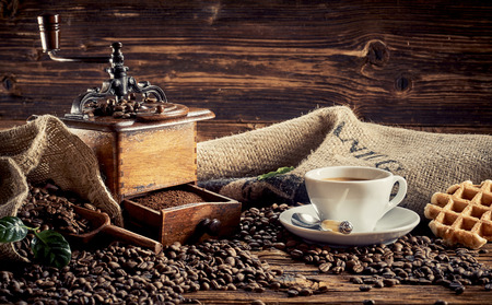 Morning cup of coffee with waffle and old fashioned wooden grinder with drawer full of ground powder surrounded by roasted beans on a rustic wood background Stock Photo