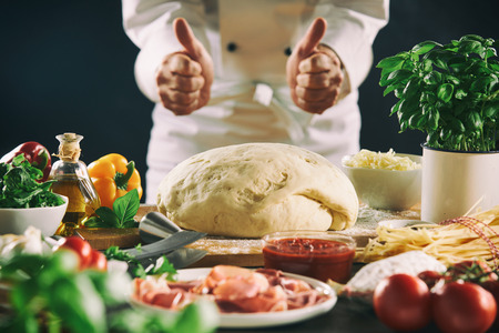 Chef giving a double thumbs up over a mound of freshly made dough left to rise for Italian cuisine with pizza and pasta ingredients