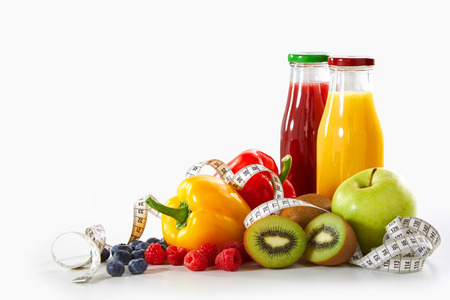 Weight loss and healthy diet concept with a tape measure entwined with assorted fresh organic fruit and vegetables