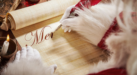 Father Christmas writing an Xmas message on a scroll in decorative calligraphic text using an old quill pen in a close up view of his hands Banque d'images - 110811730