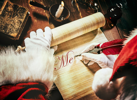 Santa Claus writing a Christmas greeting on an old scroll with a vintage quill feather pen in neat calligraphic text by candlelight viewed from above in a close up on the document Stock Photo