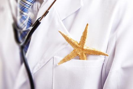 Dry starfish in doctors breast pocket in close-up
