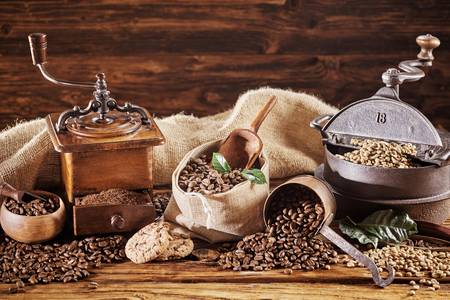 Vintage coffee panorama banner with a coffee grinder and roaster surrounded by roasted and raw beans on rustic wood with copy space Stock Photo