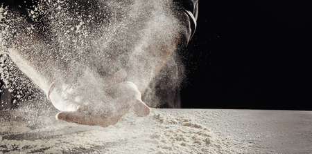 Cloud of flour caused by unidentified man cleaning off hands hands over table already covered in white powder Stockfoto
