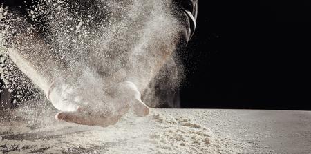 Mehlwolke, verursacht von einem unbekannten Mann, der sich die Hände abwischt, über den Tisch, der bereits mit weißem Pulver bedeckt ist