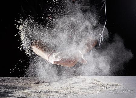 Pracownik restauracji w czarnym garniturze i lateksowych rękawiczkach wycierający białą mąkę w proszku z rąk na prostokątnym Zdjęcie Seryjne