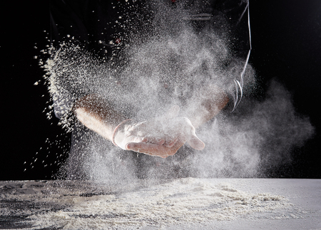 Restaurant worker in black suit and latex gloves wiping white powdery flour off hands onto rectangular Stok Fotoğraf - 110811417